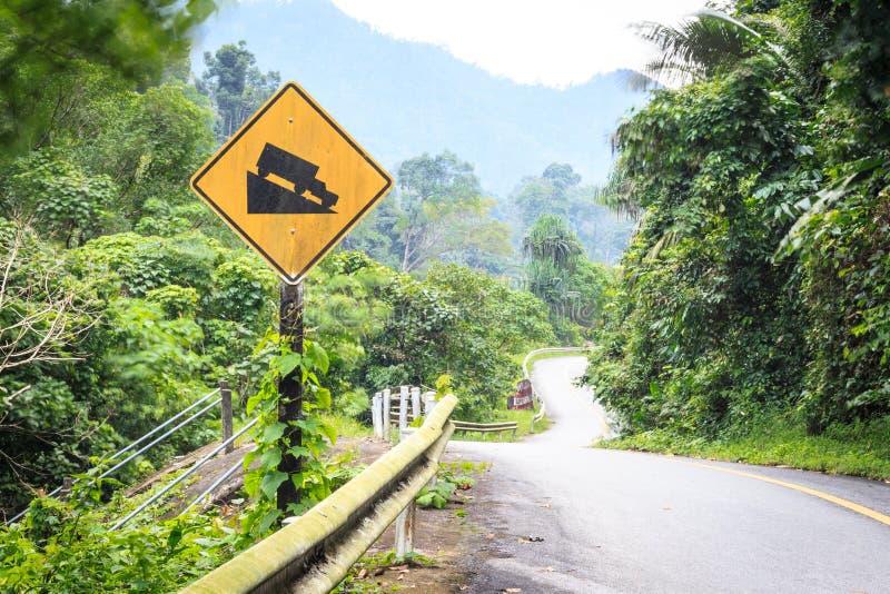 Vägmärkelutning och lastbil för varning brant på kullen royaltyfria bilder