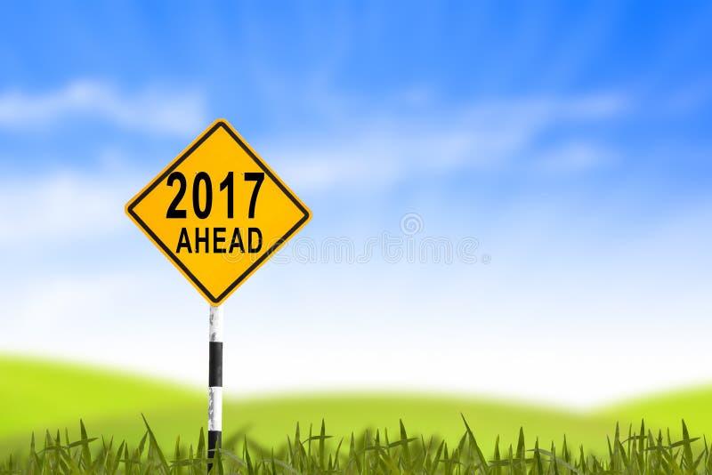 2017, vägmärket i gräsfältet till det nya året och blå himmel, kan royaltyfri bild