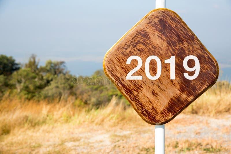 Vägmärket med 2019 på träbakgrund föreställer den nya 2019en Träbaner för nytt år 2019 royaltyfria foton