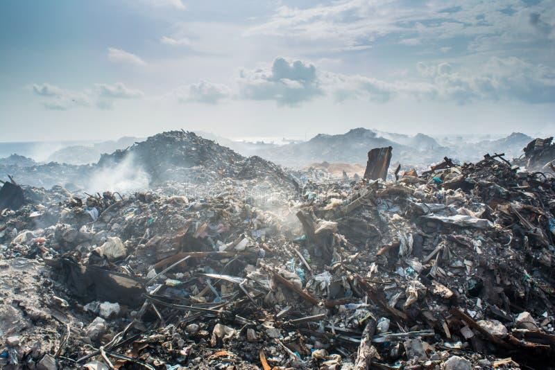 Vägra på avskrädeförrådsplatsen med lotten av rök, kull, plast-flaskor, racka ner på och kassera på den tropiska ön arkivbilder