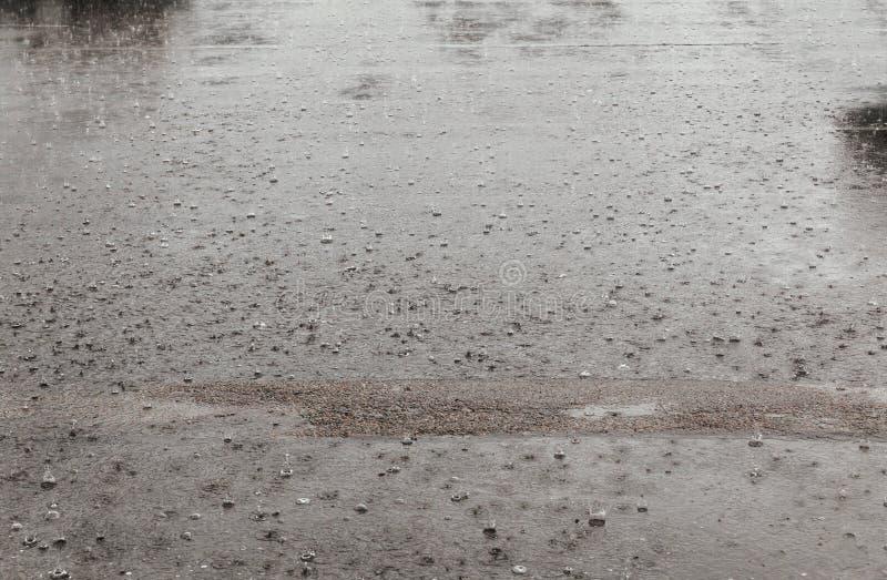 Vägregnvatten tappar bakgrund med reflexion för blå himmel och cirklar på mörk asfalt prognos arkivbilder