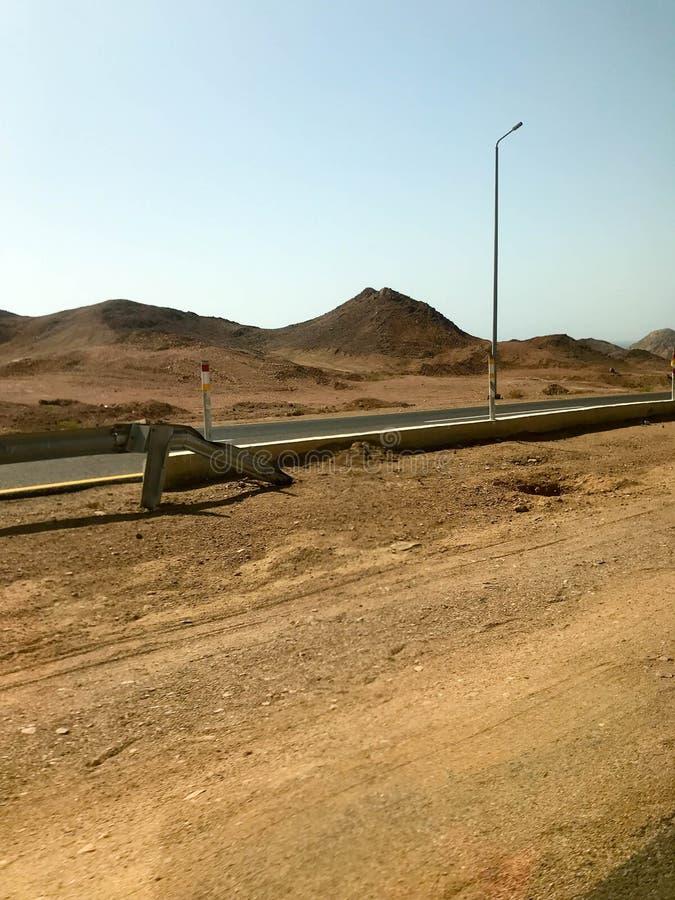 Vägrenen, huvudväg med asfalt i öknen med sand, stötdämpare och lyktstolpar, sanddyn, kullar, berg i ett varmt tropiskt arkivfoton
