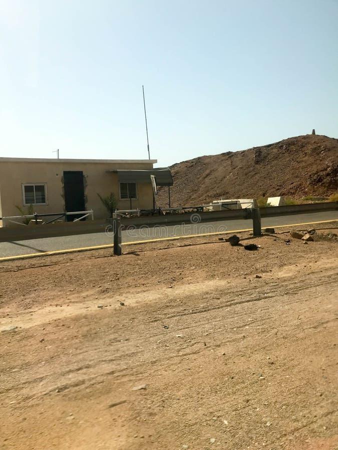 Vägrenen, huvudvägen med asfalt i öknen med sand, stötdämpare och lyktstolpar, sanddyn, kullar, berg och litet fattigt royaltyfri foto