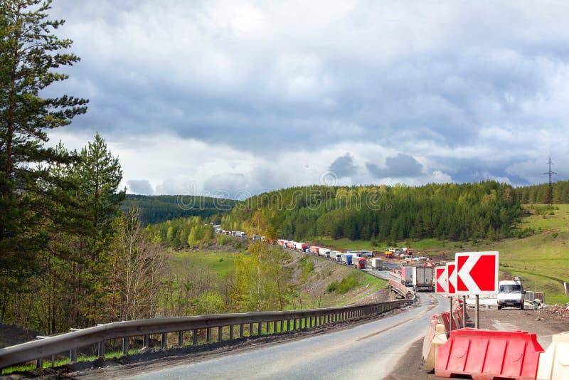 Vägreparation, rött tecken för förbikoppling, trafik på en gränd, trafikstockning, grön skog och bakgrund för molnig himmel royaltyfri fotografi
