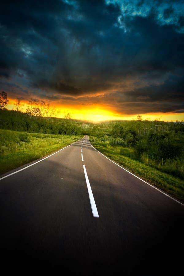vägsolnedgång till royaltyfri fotografi