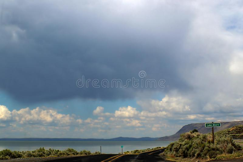 Vägtur - för grändhuvudväg för Blacktop två kurvor längs sjön Abert i Oregon in mot mountians med dramatisk stormysky fast utgift royaltyfri foto