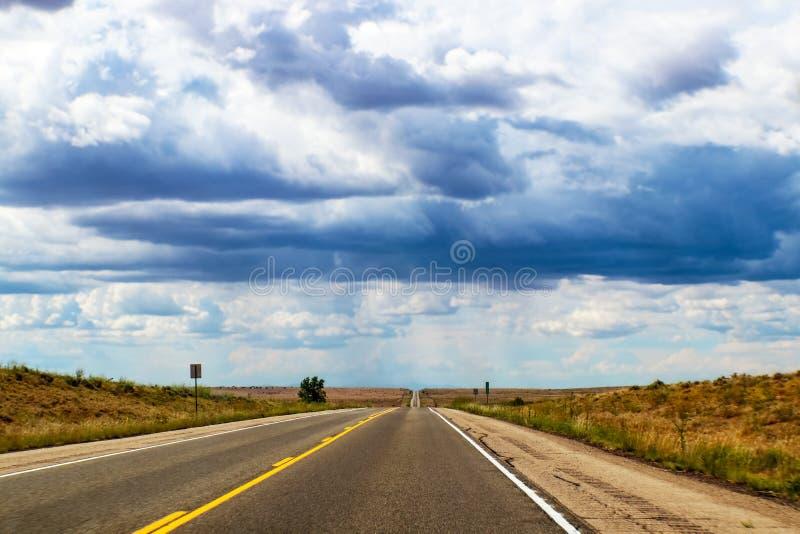 Vägtur - huvudvägen för två gränd på slättarna sträcker raksträcka över dramatisk himmel för horizonunder med konstigt ljus arkivbilder