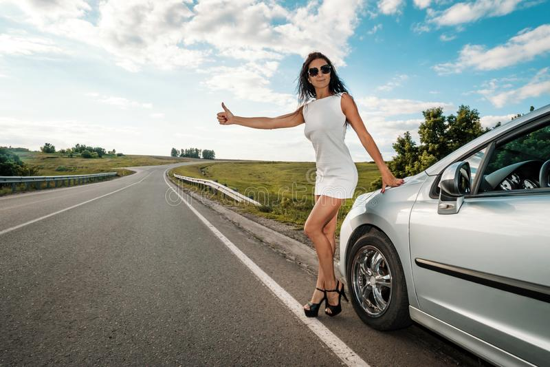 Vägturen, liftar, reser, gör en gest och folkbegreppskvinnan som liftar och stoppar bilen med tummar upp gest på fotografering för bildbyråer