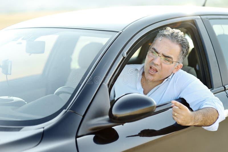Vägursinnebegrepp - den irriterade mannen skriker och gör en gest, medan köra bilen arkivfoton