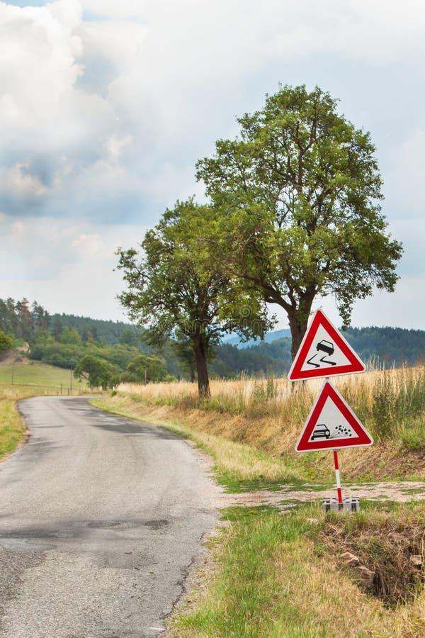 Vägvarningstecken på den hala vägen Spillt grus på vägen Landsväg i Tjeckien arkivbilder