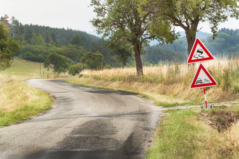 Vägvarningstecken på den hala vägen Spillt grus på vägen Landsväg i Tjeckien royaltyfri fotografi