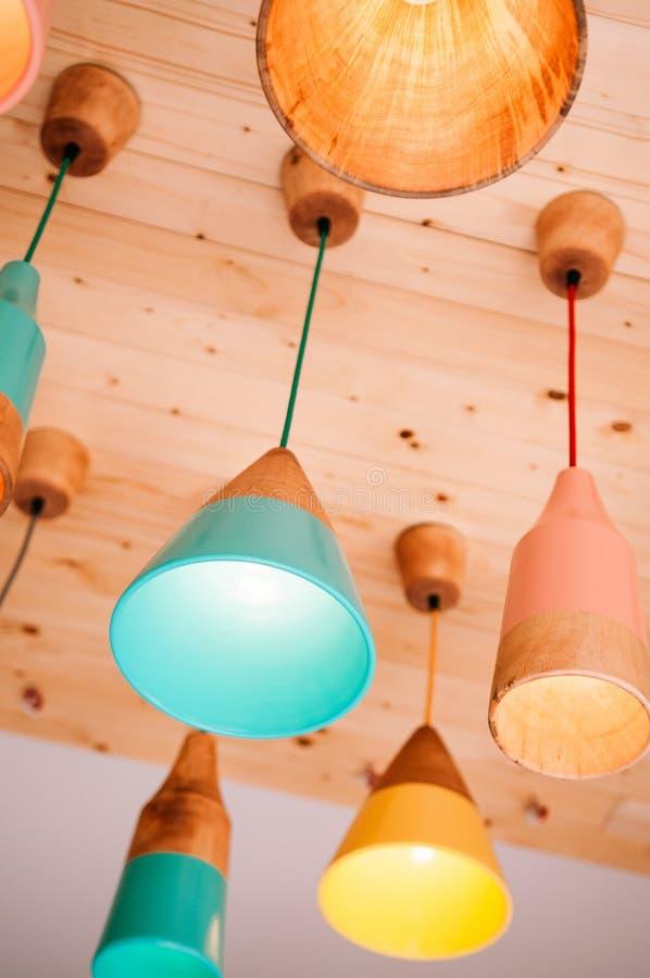 Väl pastellfärgad färgad trälampa för modern design som hänger från trätak arkivfoton