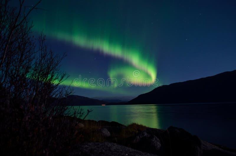 Väldig norrskendans på natthimmel över berg- och fjordlandskap arkivbild