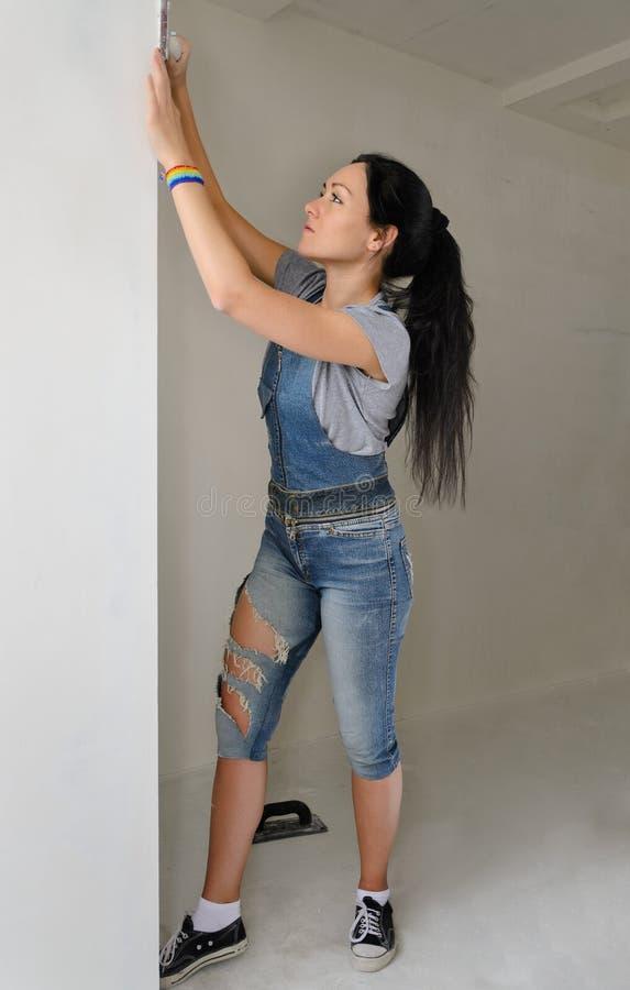 Välformad ung kvinna som nyinreder hennes lägenhet royaltyfria bilder