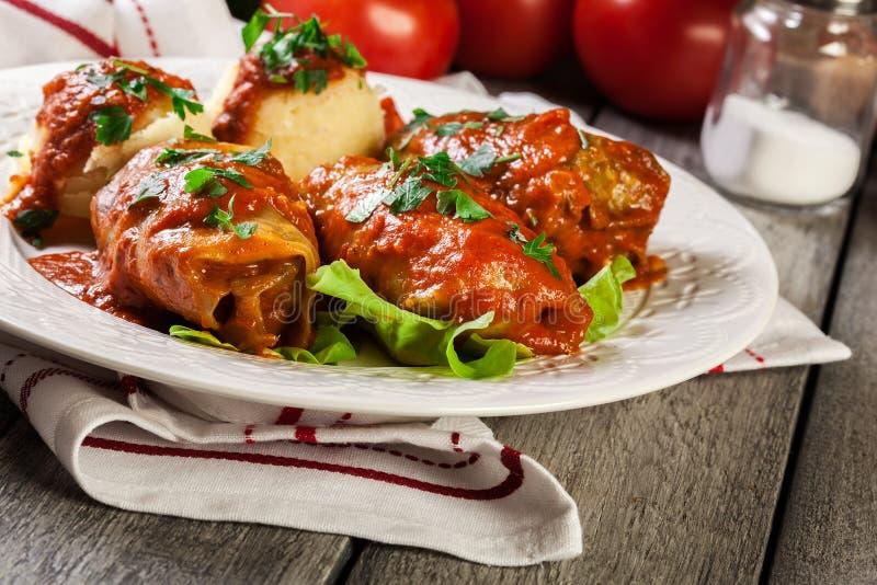 Välfylld kål med kött och ris tjänade som med kokta potatisar och tomatsås royaltyfri foto