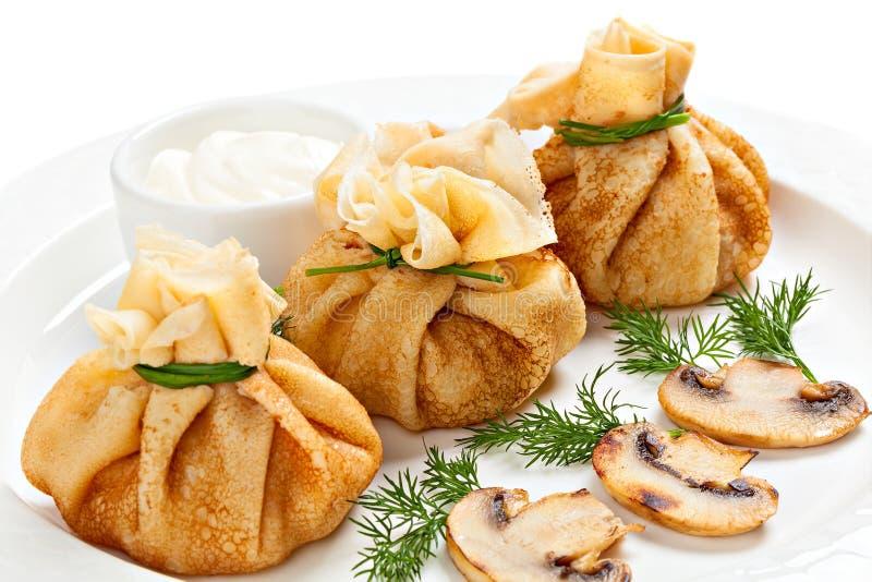 Välfyllda pannkakor med champinjoner royaltyfri bild