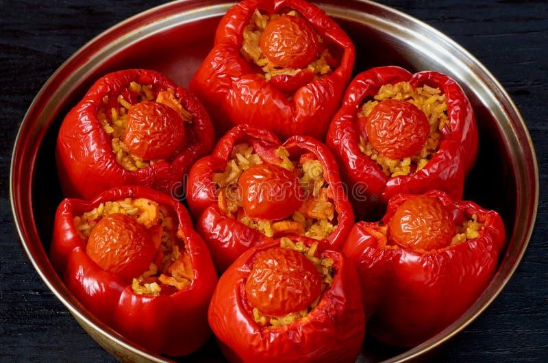 Välfyllda röda spanska peppar med ris och grönsaker i den stekheta maträtten på det svarta bakgrundsslutet upp arkivfoto