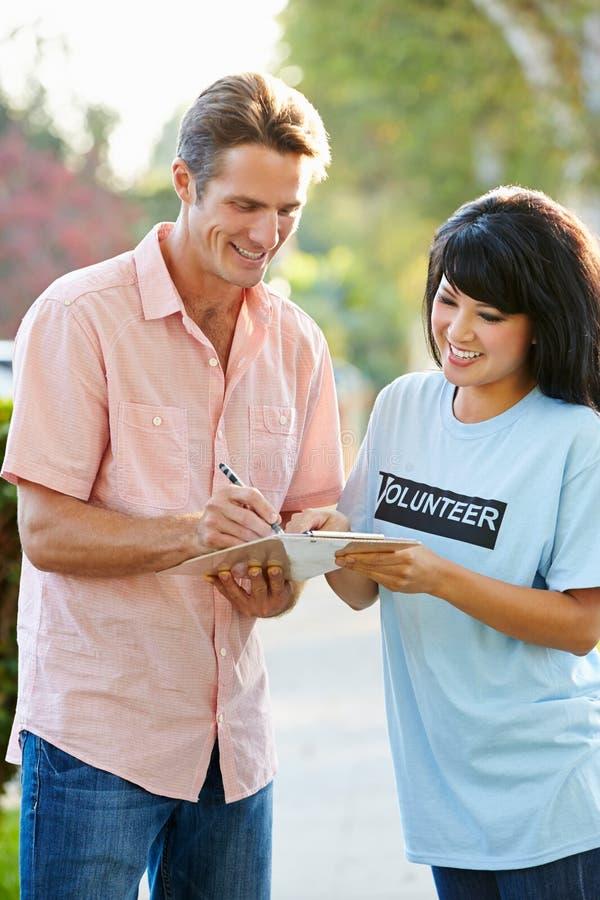 Välgörenhetarbetare som samlar sponsorskap från man i gata royaltyfri foto