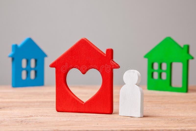 Välj ett hus för att köpa eller hyra Liten man och färgrika hus arkivbild