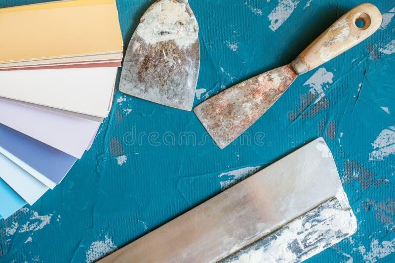 Välj färgen av målarfärg för väggarna Gamla hjälpmedel för målning och spackelväggar och bakgrunder Framställning av bakgrund royaltyfria bilder