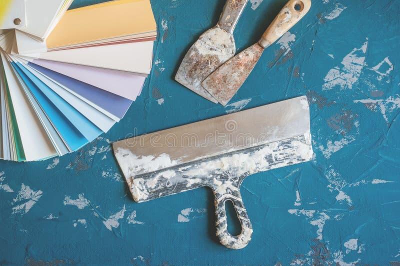 Välj färgen av målarfärg för väggarna Gamla hjälpmedel för målning och spackelväggar och bakgrunder Framställning av bakgrund arkivfoto