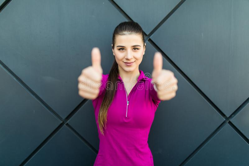 Välj helthliv Sport, kondition och folkbegrepp Den lyckliga le sportive visningen för ung kvinna tummar upp över svart streevägg  arkivbild