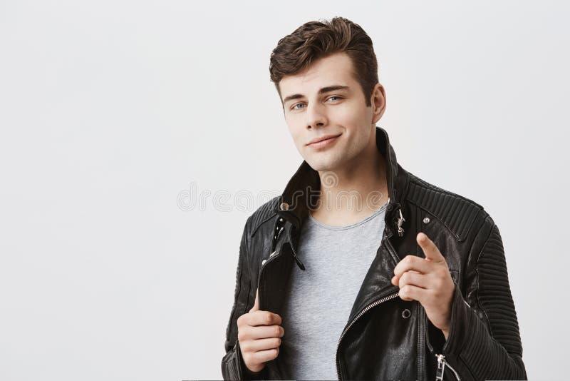 välj I dig Stilig attraktiv man i främre finger för stilfulla svarta punkter för läderomslag på kameran, blickar säkert royaltyfri fotografi