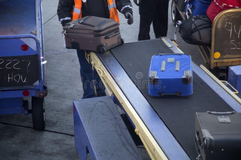 Välj upp bagage i flygplats arkivfoto