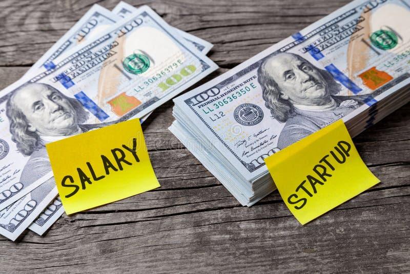 Välja liten lön eller start med stor vinst, begrepp Kontorsklistermärkear på dollarräkningar på trätabellen royaltyfria bilder