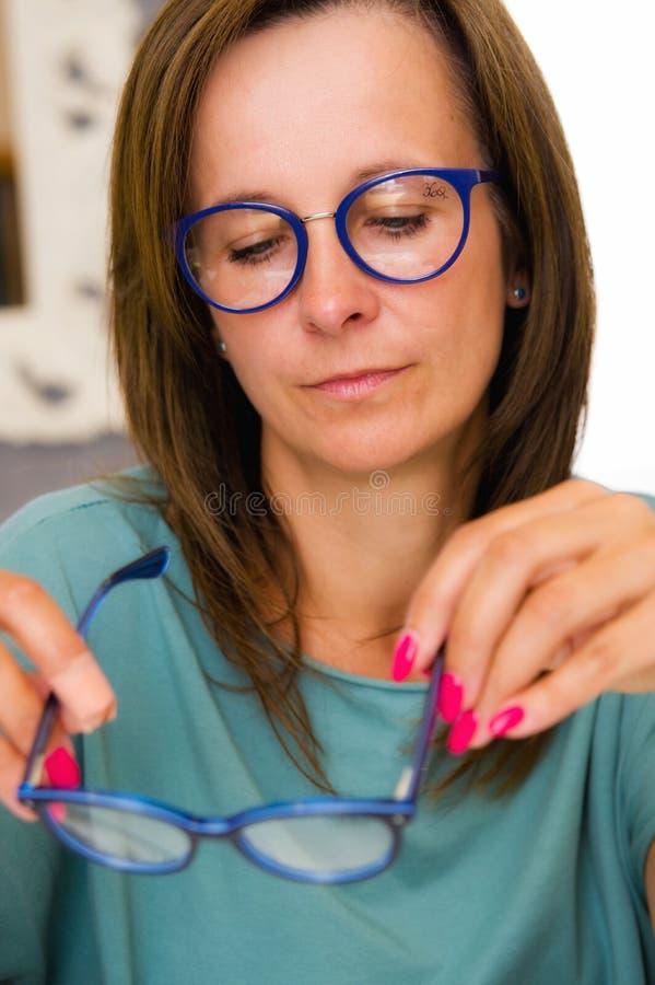 Väljande och köpande glasögon för brunettkvinna i optikersalong eller att shoppa royaltyfri bild