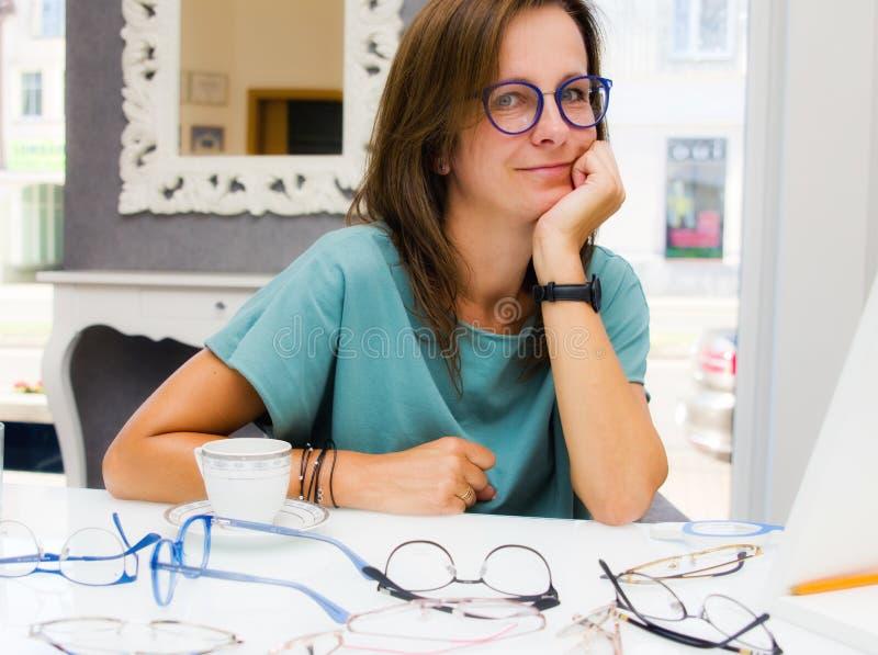 Väljande och köpande glasögon för brunettkvinna i optikersalong eller att shoppa arkivbilder