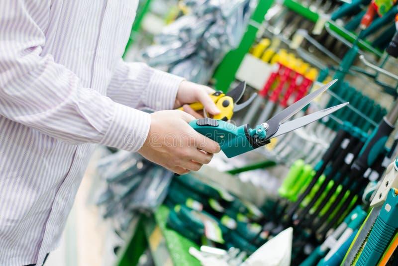 Väljande och köpande sax för att beskära brämträdgräs i avdelning för trädgårds- hjälpmedel på DIY-shoppinglagret royaltyfri fotografi