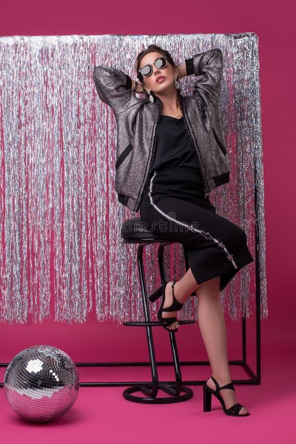Välklädd kvinna i solglasögon på stångstol arkivfoto
