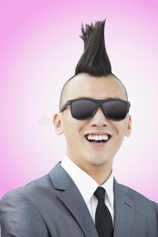 Välklädd ung man med Mohawk och solglasögon som ler, rosa bakgrund royaltyfri bild