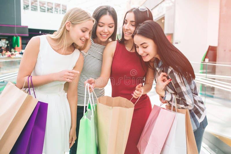 Välklädda och attraktiva unga kvinnor står tillsammans och ser in i en påse Flickan i röd klänning rymmer arkivbild