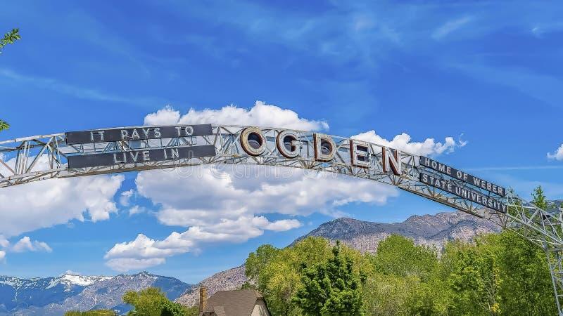 Välkommen båge för panorama på staden av Ogden Utah mot livlig blå himmel och pösiga moln arkivbild