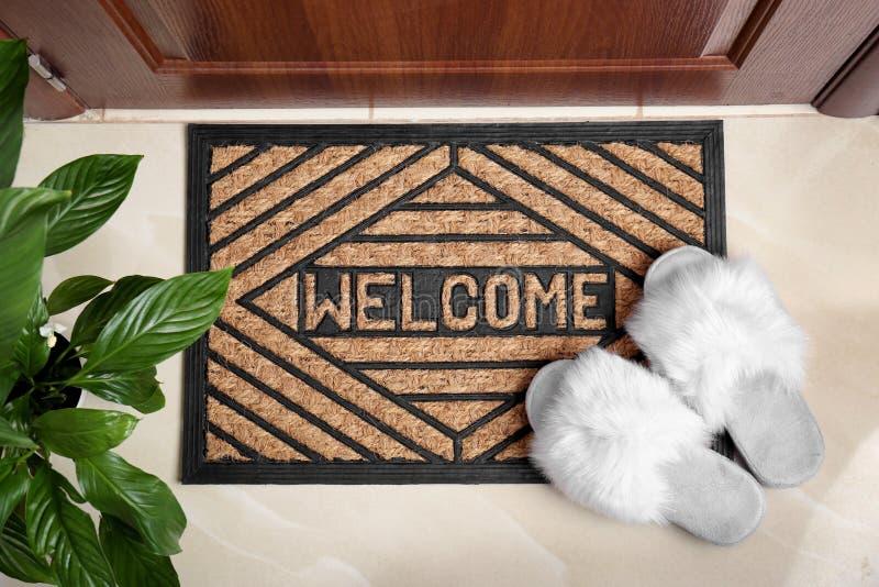 Välkommen dörrmatta och vita häftklammermatare på dörren i korridor royaltyfria foton