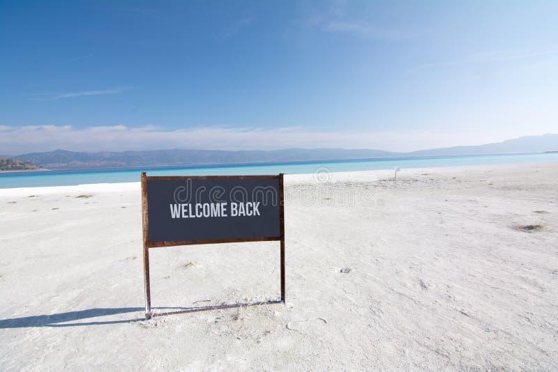 Välkommen tillbaka text på en brädestrand, kust i Turkiet arkivfoto