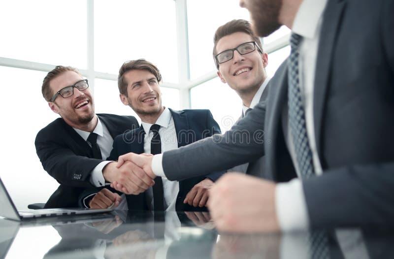 Välkommet affärsfolk som skakar händer över ett skrivbord royaltyfri bild