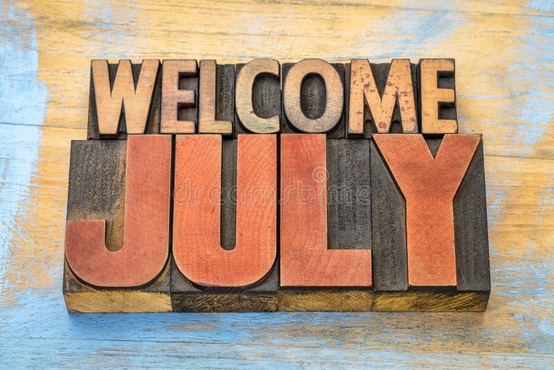 Välkommet Juli ordabstrakt begrepp i wood typ royaltyfri bild