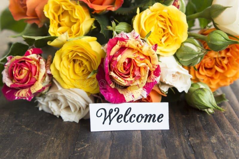 Välkommet kort med buketten av mångfärgade rosor royaltyfri bild