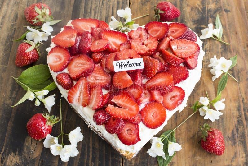Välkommet kort med formad jordgubbeostkakahjärta royaltyfri bild
