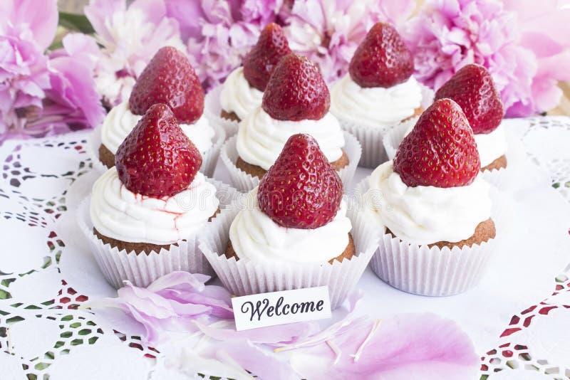 Välkommet kort med jordgubbemuffin arkivbild