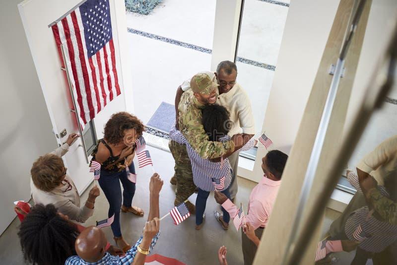 Välkomnade den manliga soldaten för den unga afrikanska amerikanen hem vid familjen för tre utveckling, högstämd sikt arkivfoton