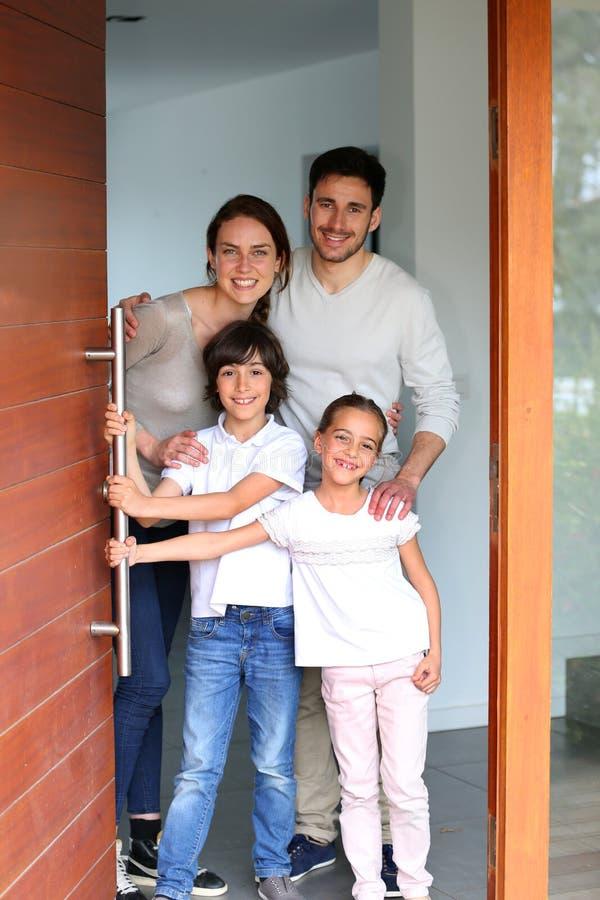 Välkomnande gäster för ung lycklig familj in i deras hem arkivfoto