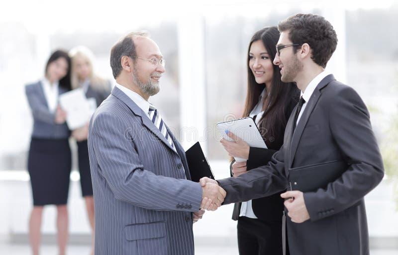 Välkomnande och handskakning av affärsfolk i kontoret royaltyfri foto