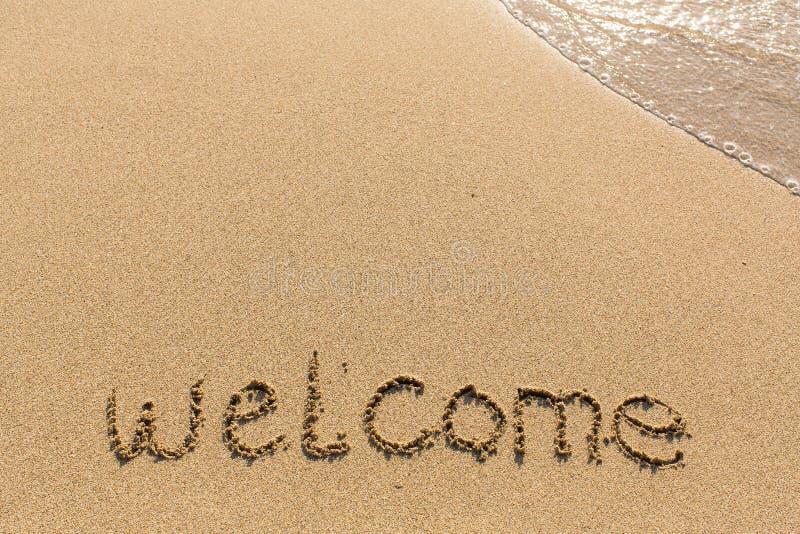 Välkomnande - ord som dras på sandstranden arkivfoton