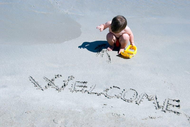 Välkomnande som skrivs i en sandig strand royaltyfria bilder