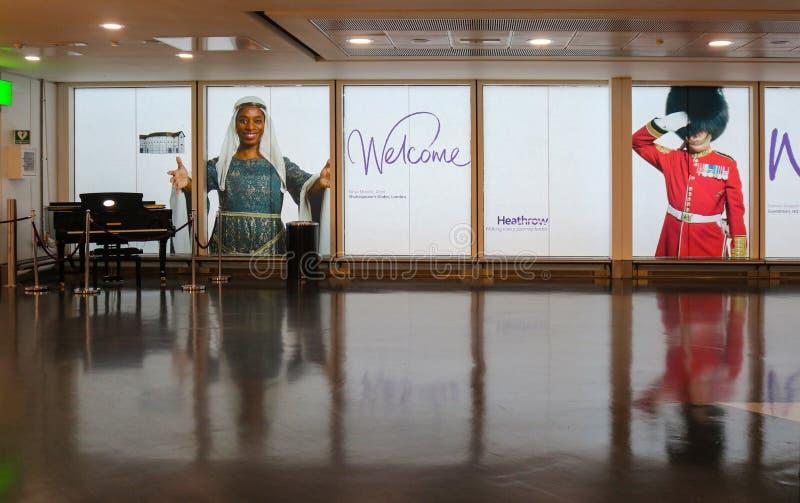 Välkomnande till den Heathrow flygplatsen - sikt med flygeln och bilder av mångkulturellt folk som hälsar handelsresande som skri arkivfoton