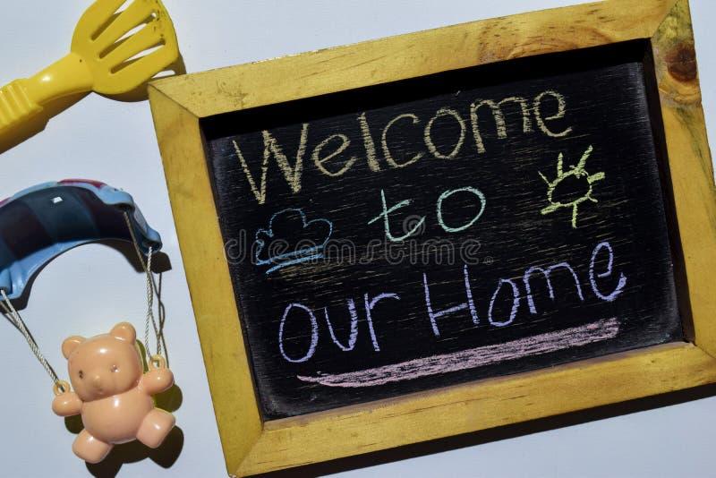 Välkomnande till Our Home på färgrikt handskrivet för uttryck på svart tavla royaltyfri fotografi